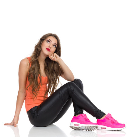 skeptic: Smiling young woman in orange shirt, black leather trousers, pink sneakers sitting on a floor and looking up. Full length studio shot isolated on white.