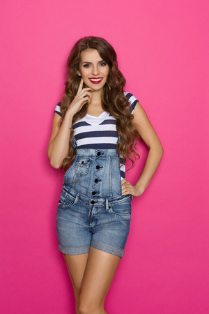 three quarter length: Cheerful beautiful young woman in dungarees holding hand on chin and looking at camera. Three quarter length studio shot on pink background.