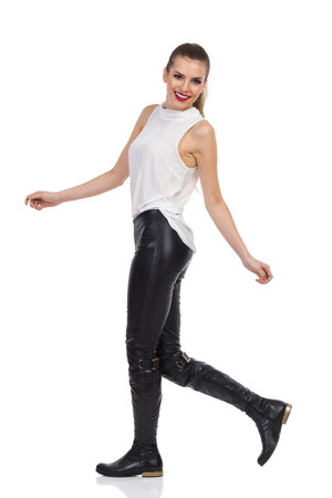 Smiling young woman in white shirt, black leather trousers and boots walking and looking at camera. Full length studio shot isolated on white.