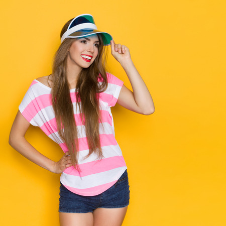 three quarter length: Smiling young woman in pink stripped shirt and blue sun visor posing with hand on hip and looking away. Three quarter length studio shot on yellow background. Stock Photo
