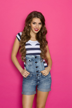 three quarter length: Beautiful girl with long hair posing in dungarees and striped shirt. Three quarter length studio shot on pink background.