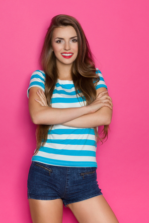 three quarter length: Beautiful young woman in striped shirt and jeans shorts posing with arms crossed. Three quarter length studio shot on pink background.