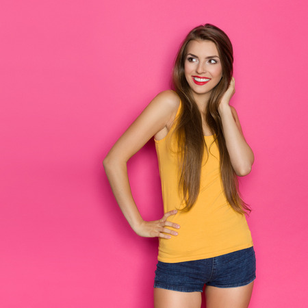 three quarter length: Young beautiful woman in jeans shorts and yellow shirt posing with hand on hip and looking away at copy space. Three quarter length studio shot on pink background.