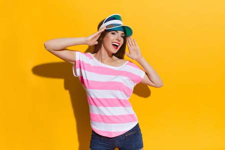 hands on waist: Shouting young woman in pink stripped shirt and blue sun visor posing and holding head in hands. Waist up studio shot on yellow background.