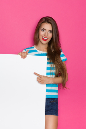background person: Beautiful young woman in striped shirt and jeans shorts posing white placard and pointing. Three quarter length studio shot on pink background.