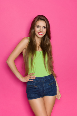 sexy woman jeans: Young beautiful woman in jeans shorts and lime green shirt posing with hand on hip and looking at camera. Three quarter length studio shot on pink background.