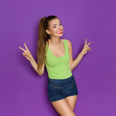 Smiling young woman in lime green shirt posing and showing peace hand sign.Three quarter length studio shot on violet background.