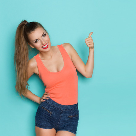 Young attractive woman in jeans shorts and orange shirt showing with thumb up. Three quarter length studio shot on a teal background.