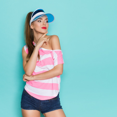 Beautiful young woman in pink striped shirt, jeans shorts and blue sun visor posing with hand on chin and looking away. Three quarter length studio shot on teal background.