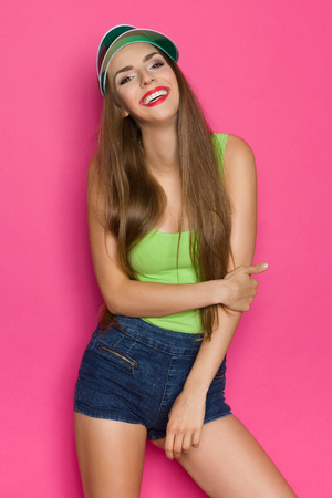 lime green background: Smiling young woman in lime green shirt, jeans shorts and green sun visor posing on pink background. Three quarter length studio shot. Stock Photo
