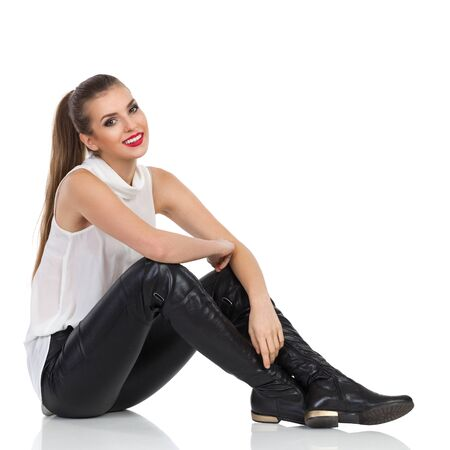 Cheerful young woman in white shirt, black leather trousers and boots sitting relaxed on a floor. Full length studio shot isolated on white