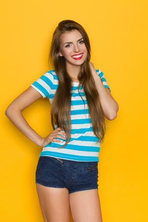 capelli lunghi: Giovane donna con i capelli lunghi e bel sorriso in posa in jeans e camicia a righe pantaloncini. Tre quarti di lunghezza in studio girato su sfondo giallo. Archivio Fotografico