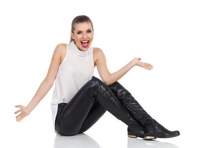 Shouting young woman in white shirt, black leather trousers and boots sitting with arms outstretched and shouting. Full length studio shot isolated on white