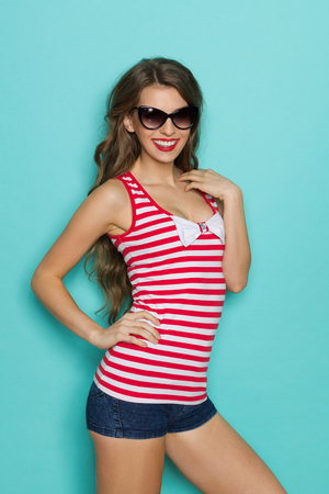 three quarter length: Smiling young woman posing in sunglasses and red striped shirt with white bow. Three quarter length studio shot on teal background.