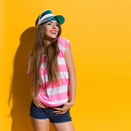 three quarter length: Smiling young woman in pink stripped shirt and blue sun visor posing and looking away. Three quarter length studio shot on yellow background. Stock Photo