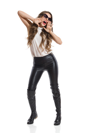 long pants: Shouting woman in black leather trousers, boots and white shirt. Full length studio shot isolated on white.