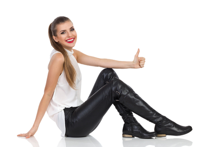 look up: Smiling young woman in white shirt, black leather trousers and boots sitting on a floor and showing thumb up. Full length studio shot isolated on white Stock Photo