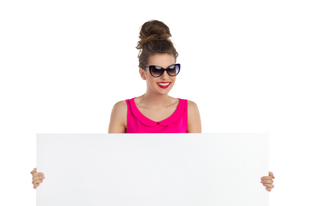 topknot: Smiling young woman in sunglasses with big hair bun holding a white banner and looking at camera. Head and shoulders studio shot isolated on white. Stock Photo
