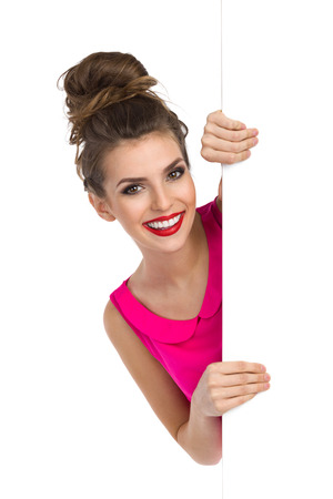 topknot: Beautiful young woman with hair bun standing behind big white banner, holding it and smiling. Studio shot isolated on white.