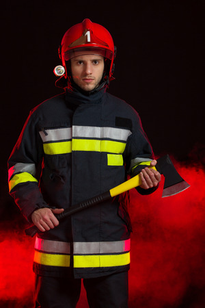 three quarter length: Serious fireman in red helmet holding an axe and standing in smoke. Three quarter length studio shot on black background.