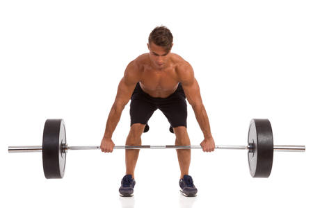 focus: Fit Man Picking Up A Barbell. Full length studio shot isolated on white. Stock Photo