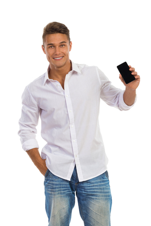 Smiling young man in white shirt and jeans standing with hand in pocket and showing the cell phone. Three quarter length studio shot isolated on white. Standard-Bild