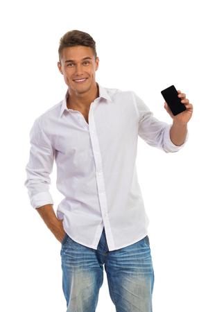 hombres jovenes: Sonriente joven en camisa blanca y pantalones vaqueros de pie con la mano en el bolsillo y que muestra el teléfono celular. Tres cuartos de longitud de tiro del estudio aislado en blanco.