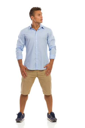 legs apart: Handsome young man in blue shirt, beige shorts and sneakers standing with legs apart and looking away. Full length studio shot isolated on white.