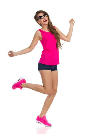 one people: Smiling young woman in sunglasses, pink shirt, jeans shorts and pink sneakers standing on one leg and smiling. Full length studio shot isolated on white. Stock Photo