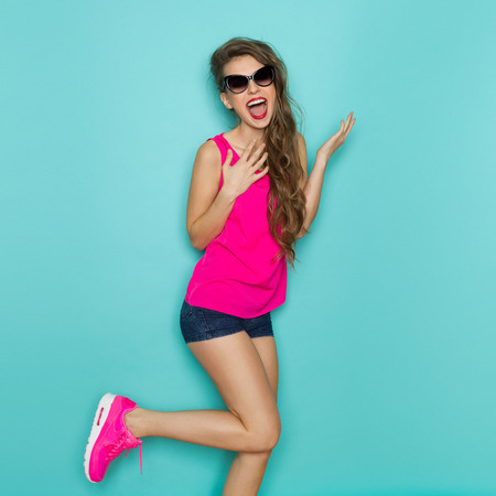 Shouting young woman in sunglasses, pink shirt, jeans shorts, and pink sneakers posing on one leg. Three quarter length studio shot on a teal background.