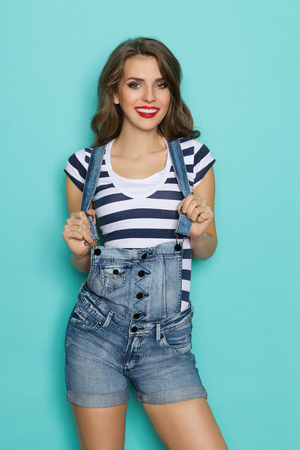 Beautiful smiling young woman in dungarees and blue striped shirt posing. Three quarter length studio shot on teal background.