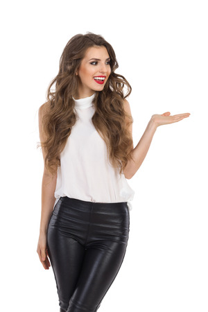 Smiling young woman in white shirt and leather trousers posing with hand raised and presenting something. Three quarter length studio shot isolated on white. Standard-Bild