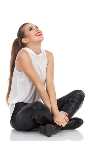 Smiling young woman in white shirt, black leather trousers and boots sitting on a floor and looking up. Full length studio shot isolated on white.