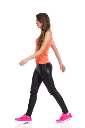 profile view: Young woman in orange shirt, black leather trousers, pink sneakers walking and looking away. Full length studio shot isolated on white. Stock Photo
