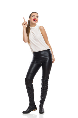 woman posing: Smiling elegance young woman in black leather trousers, boots and white shirt, pointing up and looking. Full length studio shot isolated on white.