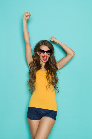 three quarter length: Shouting young woman in jeans shorts and orange shirt posing with arm raised. Three quarter length studio shot on teal background.