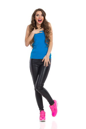 long pants: Surprised young woman in blue shirt, black leather trousers, and pink sneakers standing on one leg, holding hand on chest and looking at camera. Full length studio shot isolated on white. Stock Photo