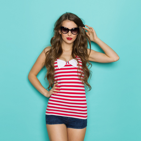 nude young: Shirt With A White Ribbon. Sexy young woman in sunglasses posing in red striped shirt with cleavage and white bow. Three quarter length studio shot on a teal background.