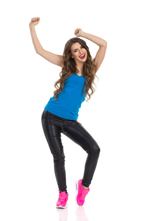 gente bailando: Mujer feliz en camisa azul, pantalones de cuero negro y zapatillas de color rosa bailando con los brazos levantados. Vista frontal. Estudio de longitud completa aislado disparo en blanco.
