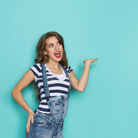 Excited woman in dungarees and blue striped shirt presenting product and looking at copy space. Three quarter length studio shot on teal background.