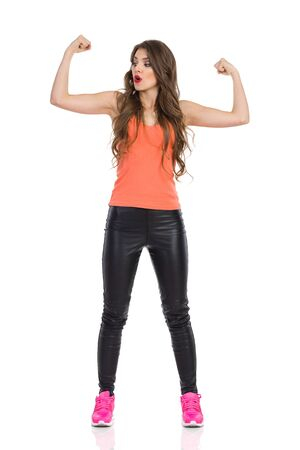 Surprised young woman in black leather trousers, orange shirt and pink sneakers, standing with arms outstretched and flexing biceps. Full length studio shot isolated on white.