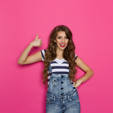 three quarter length: Smiling beautiful young woman in dungarees showing thumb up. Three quarter length studio shot on pink background.