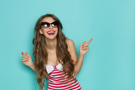 nude young: Laughing sexy young woman in sunglasses, red striped shirt with cleavage. Three quarter length studio shot on a teal background.