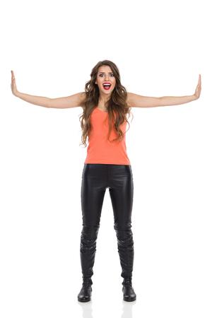 plan �loign�: femme Shocked debout avec les bras tendus et les murs pressants faux. La pleine longueur tourn� en studio isol� sur blanc.