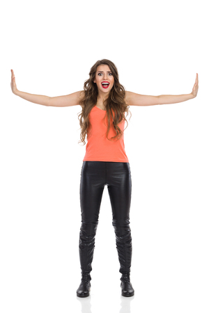 shocked: Shocked woman standing with arms outstretched and pressing fake walls. Full length studio shot isolated on white.