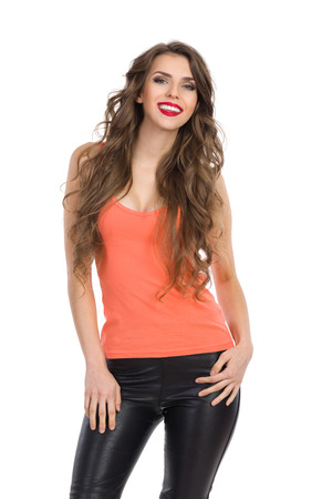 neckline: Smiling young woman in orange shirt with sexy neckline standing and looking at camera. Three quarter length studio shot isolated on white.
