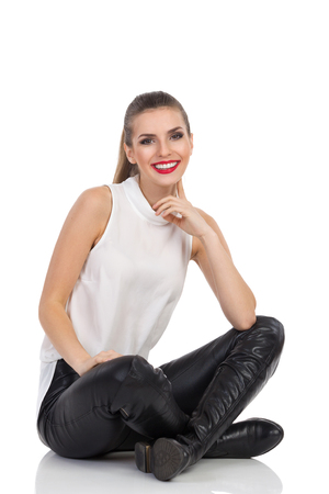 finger crossed: Smiling young woman in white shirt, black leather trousers and boots sitting on a floor with legs crossed, holding finger on chin and looking at camera. Full length studio shot isolated on white.