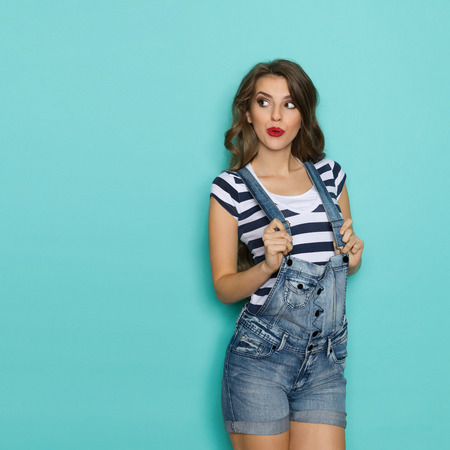 Surprised Woman In dungarees Looking At Copy Space Stockfoto