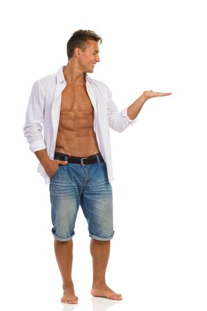 unbuttoned: Fit young man in unbuttoned white shirt and jeans shorts standing barefoot holding open hand, presenting something and looking away. Full length studio shot isolated on white.