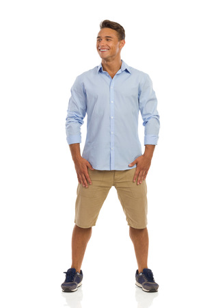legs apart: Smiling handsome young man in blue shirt, beige shorts and sneakers standing with legs apart and looking away. Full length studio shot isolated on white.